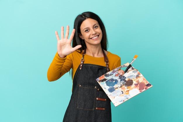 Kaukasische frau des jungen künstlers, die eine palette lokalisiert auf blauem hintergrund hält, die fünf mit den fingern zählt