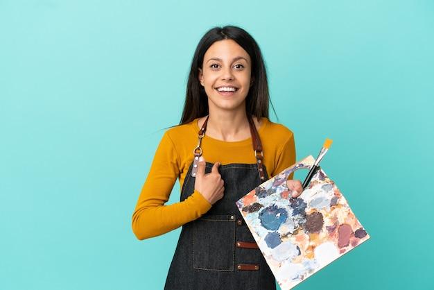 Kaukasische frau des jungen künstlers, die eine palette lokalisiert auf blauem hintergrund mit überraschtem gesichtsausdruck hält
