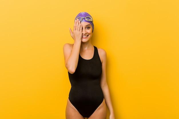 Kaukasische frau des jungen schwimmers, die den spaß bedeckt halbes gesicht mit palme hat.