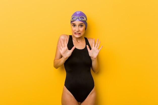 Kaukasische frau des jungen schwimmers, die jemand zeigt eine geste des ekels zurückweist.