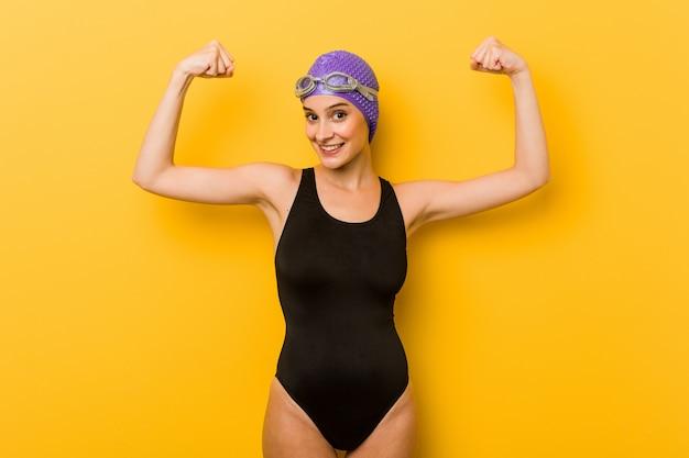 Kaukasische frau des jungen schwimmers, die stärkegeste mit den armen, weibliche energie des symbols zeigt