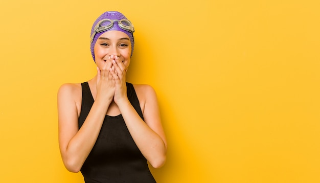 Kaukasische frau des jungen schwimmers, die über etwas, mund mit den händen bedeckend lacht.