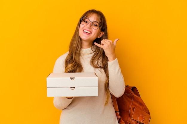 Kaukasische frau des jungen studenten, die pizzas über lokalisiertem hintergrund hält, der eine handyanrufgeste mit den fingern zeigt.