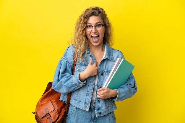 Kaukasische frau des jungen studenten lokalisiert auf gelbem hintergrund mit überraschtem gesichtsausdruck