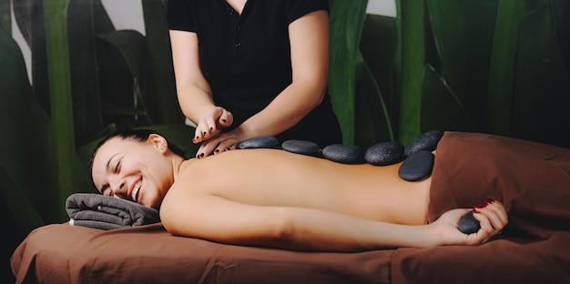 Kaukasische frau, die an der spa-massage mit steinen auf ihrem rücken lächelt, die auf der couch nahe dem spa-arbeiter liegen