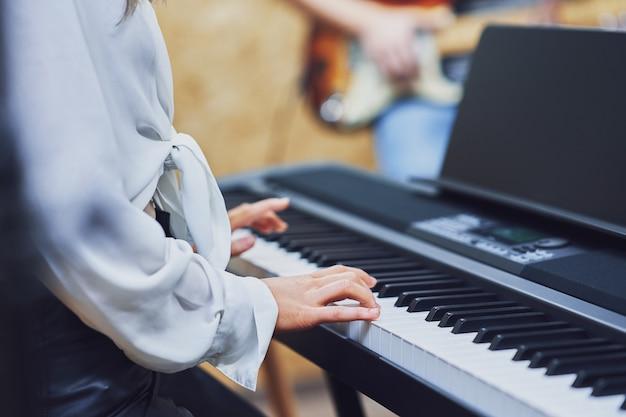 Kaukasische frau, die auf der tastatur in der band spielt