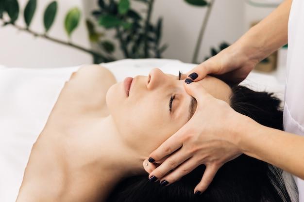 Kaukasische frau, die auf einem spa-bett liegt, erhält eine gesichtsmassage mit ätherischem aromaöl-hautpflege