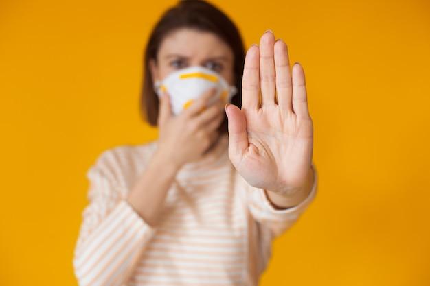 Kaukasische frau, die auf einer gelben wand aufwirft, deutet auf das stoppschild, während sie eine maske mit filter trägt