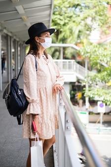 Kaukasische frau, die auf u-bahn-kreuzung in der medizinischen gesichtsmaske während der pandämie in der stadt bangkok geht.