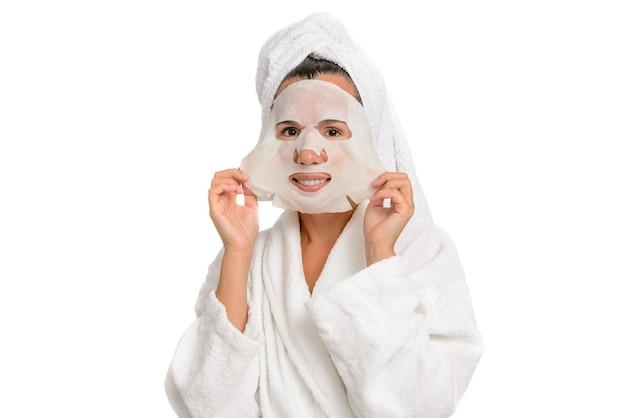 Kaukasische frau, die einen weißen kittel und ein handtuch auf dem kopf trägt, trägt eine feuchtigkeitsspendende maske auf ihr gesicht auf