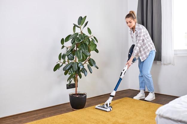 Kaukasische frau, die freizeitkleidung trägt, die den hausboden im wohnzimmer mit einem modernen staubsauger säubert, während sie zu hause bleibt und die freizeit über die tägliche reinigungsroutine zu hause nutzt