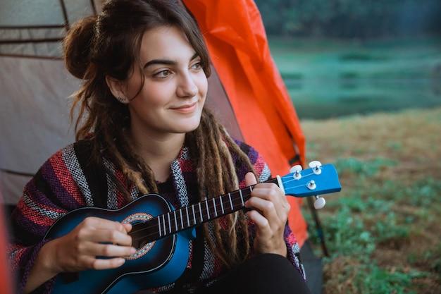 Kaukasische frau, die gitarre nach dem aufwachen spielt