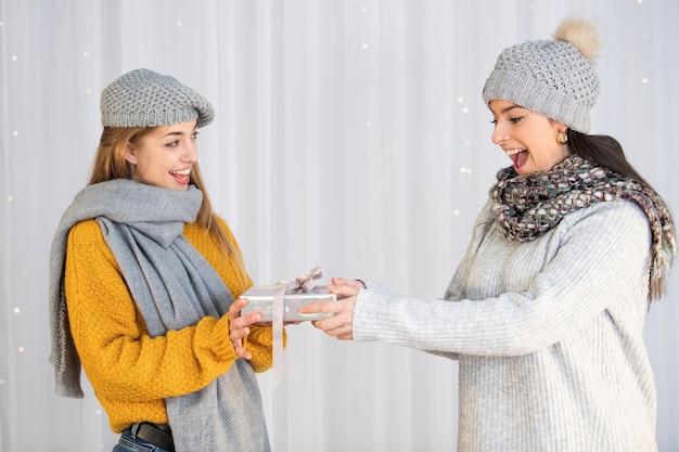 Kaukasische frau, die ihrem freund ein weihnachtsgeschenk gibt