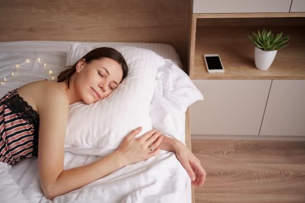 Kaukasische frau, die im bett schläft. dame genießt frische weiche bettwäsche und matratze im schlafzimmer