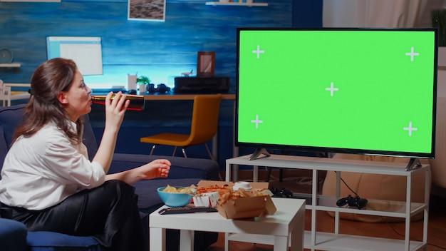 Kaukasische frau, die im fernsehen einen grünen bildschirm sieht