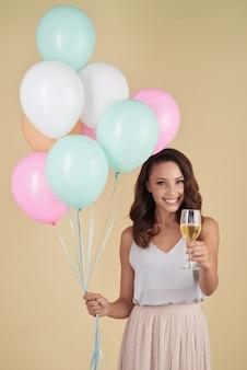 Kaukasische frau, die im studio mit bündel heliumballonen und -champagner aufwirft