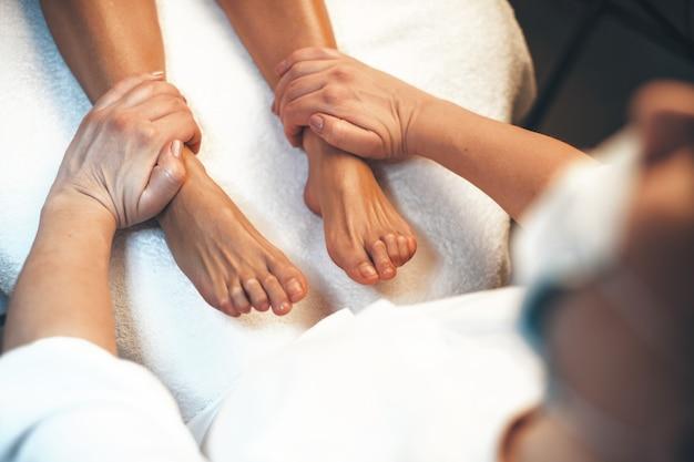 Kaukasische frau, die in einem spa-salon liegt, der eine fußmassage von einem professionellen arbeiter hat