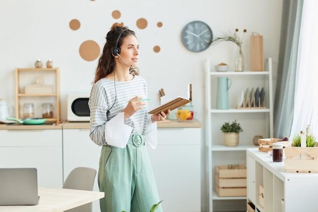Kaukasische frau, die in ihrer küche zu hause steht und notizbuch und stift hält, die mit ihren kollegen während des online-treffens zusammenarbeiten