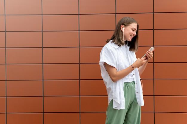 Kaukasische frau, die jemandem auf ihrem smartphone eine sms schreibt