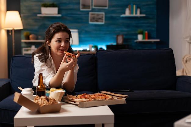 Kaukasische frau, die köstliche pizzascheibe hält und essen zum mitnehmen isst