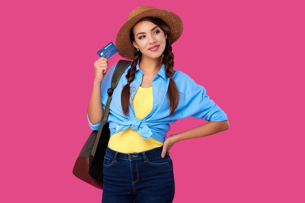 Kaukasische frau, die kreditkarte lokalisiert auf rosa hintergrund hält. online-shopping, e-commerce, internet-banking, geld ausgeben, lebenskonzepte genießen