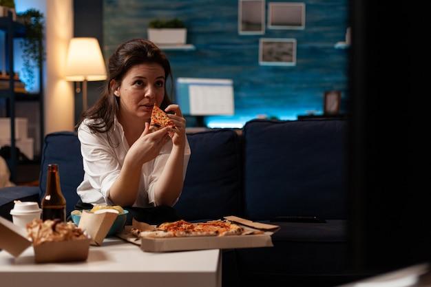 Kaukasische frau, die leckeres leckeres pizzastück isst, das fastfood nach hause geliefert hat