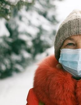 Kaukasische frau, die medizinische maske trägt, die zur kamera an der straße der stadt in der winterzeit schaut. sicherheit an öffentlichen orten während des ausbruchs des coronavirus.