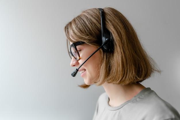 Kaukasische frau, die mit headset arbeitet, das geschäftsanrufe als dispatcher des technischen unterstützungs-isolierten copyspace beantwortet