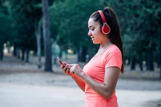 Kaukasische frau, die musik in einem park hört
