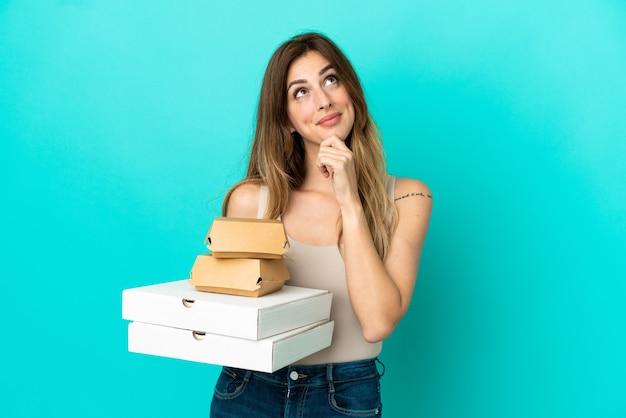 Kaukasische frau, die pizza und burger auf blauem hintergrund hält und nach oben schaut