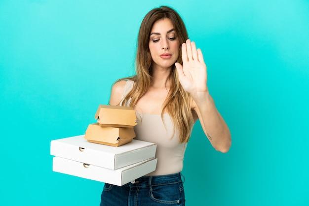 Kaukasische frau, die pizza und burger einzeln auf blauem hintergrund hält, stoppgeste macht und enttäuscht