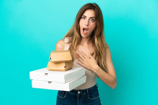 Kaukasische frau, die pizza und burger einzeln auf blauem hintergrund hält, überrascht und schockiert, während sie nach rechts schaut