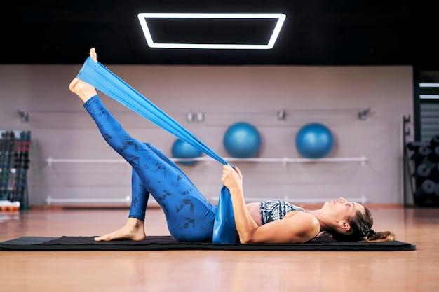 Kaukasische frau, die robuste gummibandübungen der pilates-fitness in einem modernen fitnessstudio ausübt.