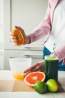 Kaukasische frau, die saft von einer orange drückt, die nahe einem glas des natürlichen getränks aufwirft