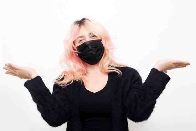 Kaukasische frau, die schwarze maske mit handflächen nach oben trägt