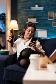 Kaukasische frau, die sich auf der couch entspannt, die in sozialen medien mit smarhphone surft