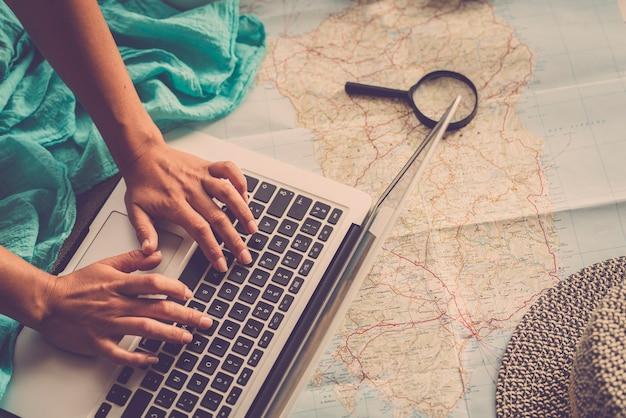 Kaukasische frau, die urlaubsreise mit laptop und kartenführer zu hause plant, planen weibliche leute nächsten urlaub, während sie sich auf dem boden entspannen