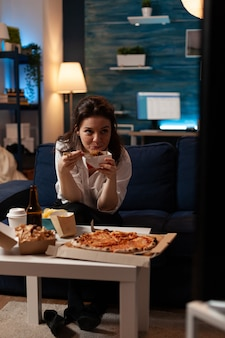 Kaukasische frau, die während der lieferung von speisen zum mitnehmen einen unterhaltungsfilm im fernsehen sieht