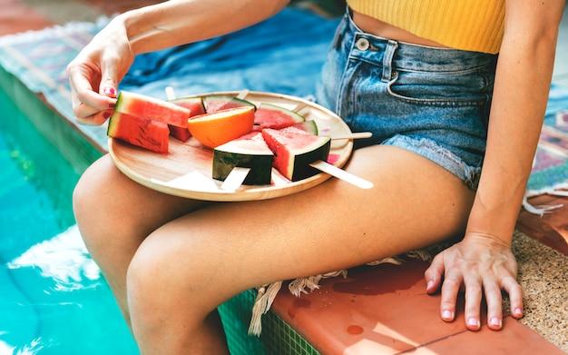 Kaukasische frau, die wassermelone in der sommerzeit isst