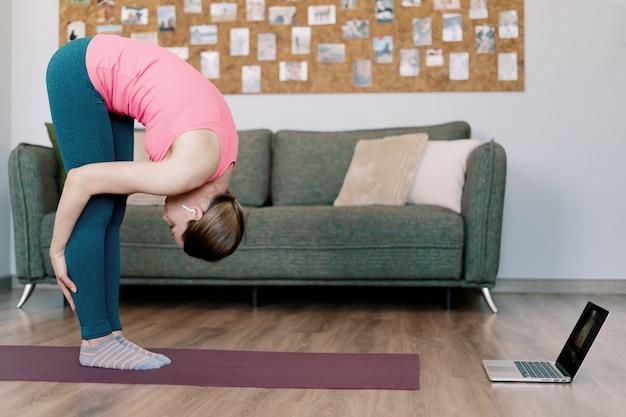 Kaukasische frau, die yoga zu hause praktiziert