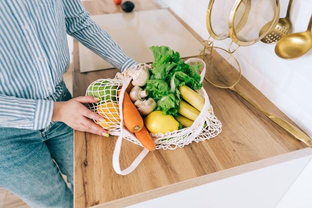 Kaukasische frau halten öko-netzbeutel mit frischem gemüse in der modernen küche.