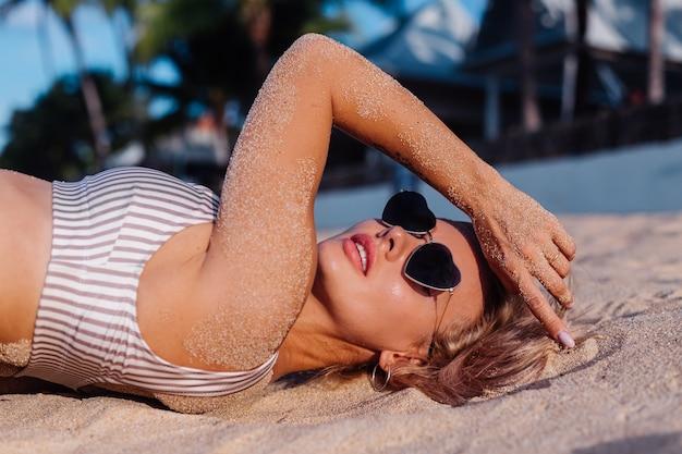 Kaukasische frau im bikini und in der sonnenbrille am tropischen strand