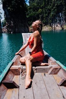 Kaukasische frau im roten sommerkleid auf thailändischem asiatischem boot im urlaub, reisen um thailand