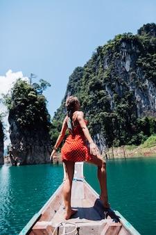 Kaukasische frau im roten sommerkleid auf thailändischem asiatischem boot im urlaub