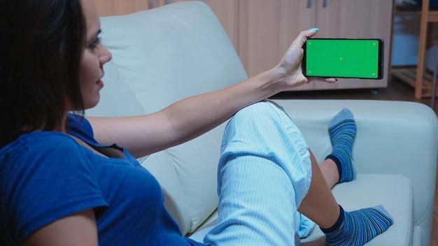Kaukasische frau im schlafanzug, die smartphone mit grünem bildschirm betrachtet. dame mit einem handy mit mockup-vorlage chroma-key isolierte handy-anzeige mit technologie-internet