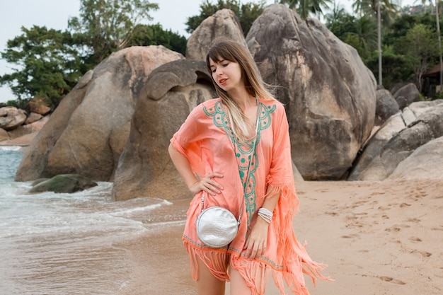 Kaukasische frau im tropischen sommer-boho-kleid, das auf dem strand geht.