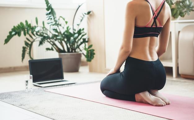 Kaukasische frau in aktiver kleidung unter verwendung eines laptops auf dem boden, der fitness tut