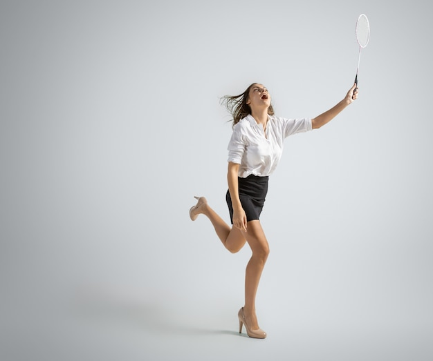 Kaukasische frau in bürokleidung spielt badminton isoliert auf grauer wand