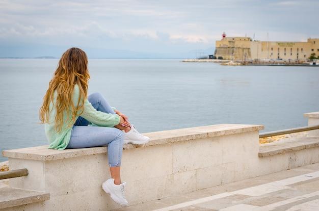 Kaukasische frau in der übergroßen strickjacke, in jeans und in turnschuhen, die auf brüstung nahe bei dem tyrrhenischen meer in gaeta, italien sitzen.