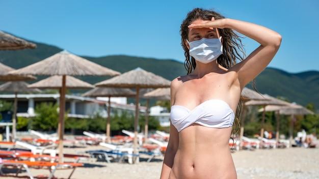 Kaukasische frau in der weißen medizinischen maske mit erhöhter hand, zum der augen vom sonnenlicht im badeanzug an einem strand in asprovalta, griechenland zu bedecken